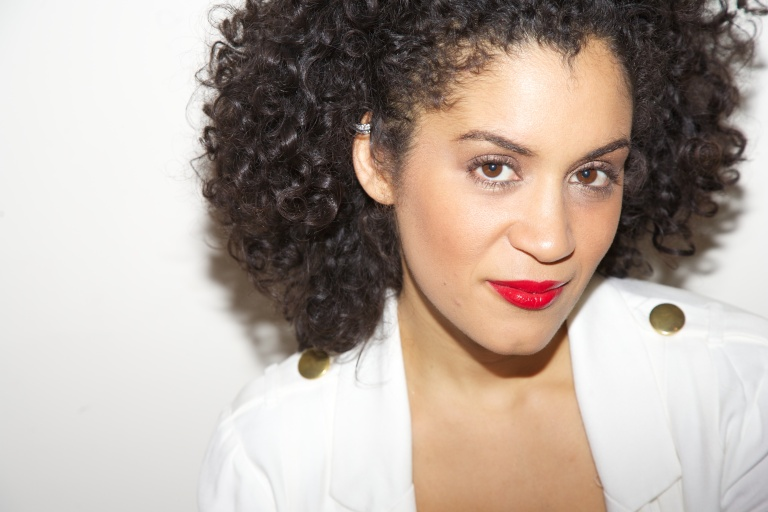 Woman with black dress, white jacket, natural makeup and curly hair